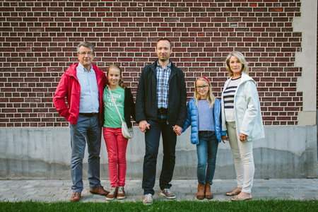 Three generation family standing by brick wall LANG_EVOIMAGES
