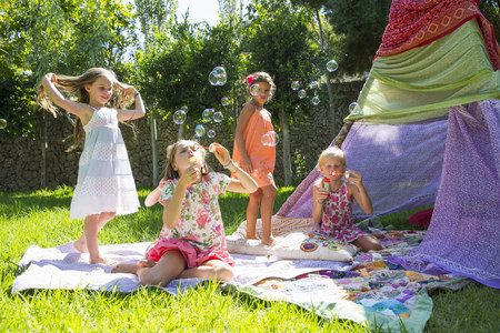 sit down: Girls blowing bubbles in summer garden party LANG_EVOIMAGES