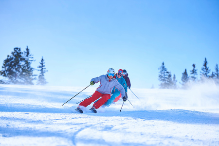 swerving: Row of male and female skiers skiing down snow covered ski slope, Aspen, Colorado, USA