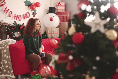 Sad young woman sitting alone on sofa at christmas LANG_EVOIMAGES