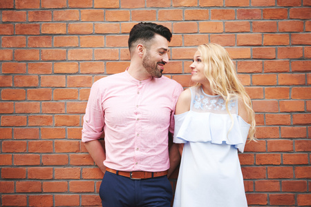 Portrait of couple in front of brick wall face to face smiling