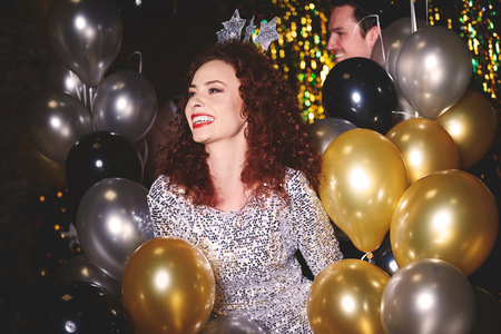 Young woman at party, surrounded by balloons LANG_EVOIMAGES