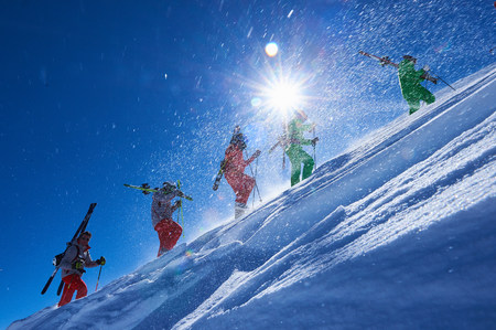 skiers: Five male skiers trudging up steep sunlit mountainside, Aspen, Colorado, USA LANG_EVOIMAGES