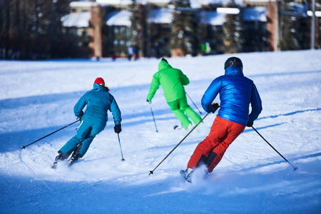 swerving: Rear view of male and female skiers skiing down snow covered ski slope, Aspen, Colorado, USA