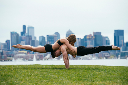 Young woman balancing on top of man in prone position, practicing yoga in front of Seattle skyline