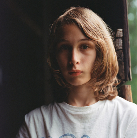 Portrait of boy with long hair, pensive expression LANG_EVOIMAGES
