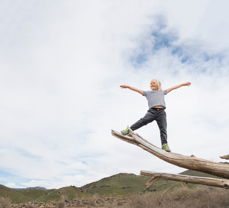 Boy balancing on end of tree trunk, sky in background