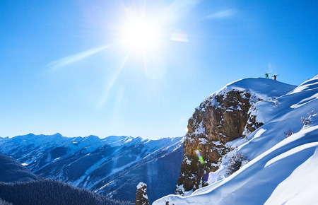 skiers: Distant view of two male skiers trudging up snow covered ridge, Aspen, Colorado, USA
