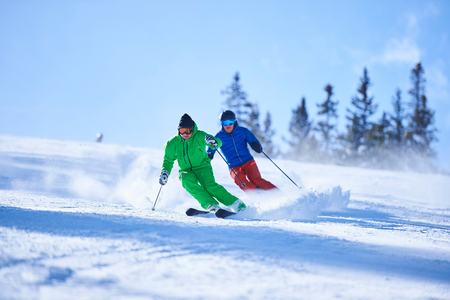 swerving: Two men skiing down snow covered ski slope, Aspen, Colorado, USA