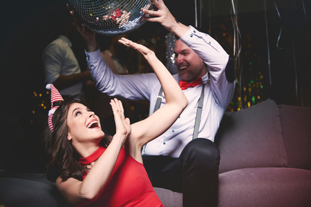 Man and woman fooling around at party, man holding disco ball above womans head LANG_EVOIMAGES