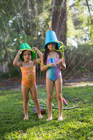 7 8: Girls with buckets on head playing with garden sprinkler LANG_EVOIMAGES