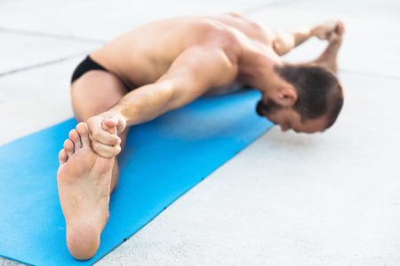 Man practicing yoga, sitting on yoga mat doing the splits and touching toes