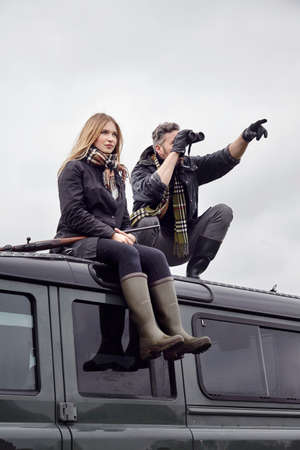 Hunting couple, on top of off road vehicle with shot gun and binoculars