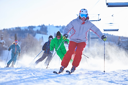 swerving: Male and female skiers skiing on snow covered ski slope, Aspen, Colorado, USA LANG_EVOIMAGES