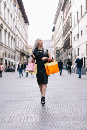 Stylish mature female shopper strolling down street,Florence,Italy