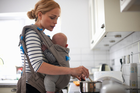 strapped: Woman cooking in kitchen,baby strapped to body in sling