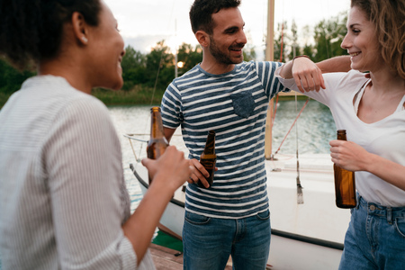 near beer: Three friends on pier,beside boat,relaxing,holding bottles of beer