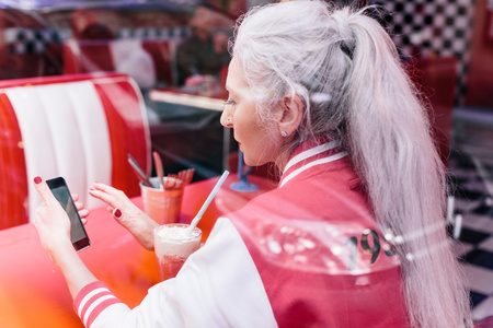 vintage: Mature woman in baseball jacket looking at smartphone in 1950s diner LANG_EVOIMAGES
