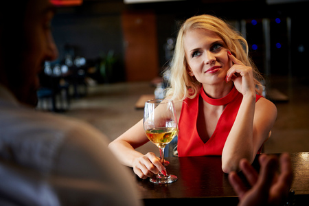 sultry: Young woman flirting with barman sitting at bar