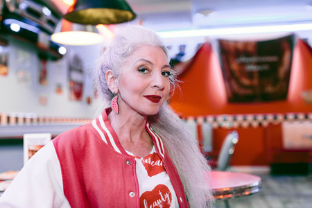 people: Portrait of mature woman in baseball jacket in 1950s diner