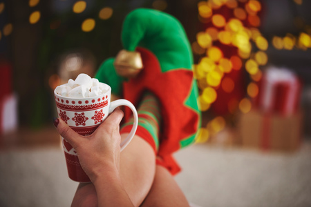 Woman wearing elf slippers holding hot chocolate LANG_EVOIMAGES