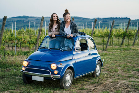 Tourists standing through car sunroof,vineyard,Tuscany,Italy