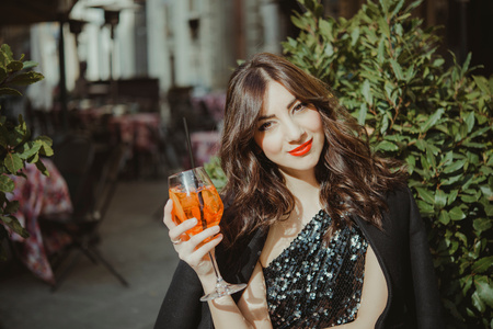Portrait of young woman,outdoors,raising glass LANG_EVOIMAGES
