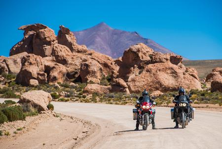 Motorcyclists riding motorcycles on dusty road,Uyuni,Oruro,Bolivia,South America
