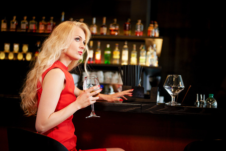 Glamorous young woman with long blond hair waiting at bar
