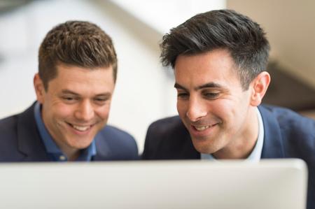 Dos hombres de negocios mirando la computadora en la oficina