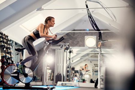 Young woman training,pedalling exercise bike in gym LANG_EVOIMAGES