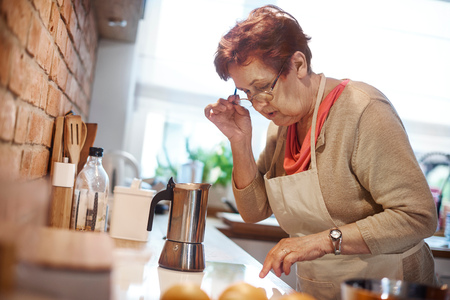 trapped: Senior adult woman learning to use electric hob to make coffee
