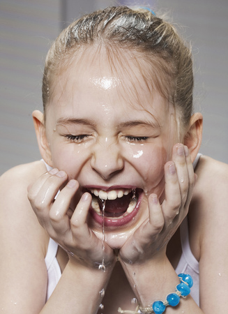 Laughing girl washing her face LANG_EVOIMAGES