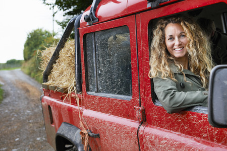 leaning on the truck: Mother driving 4x4 on the farm