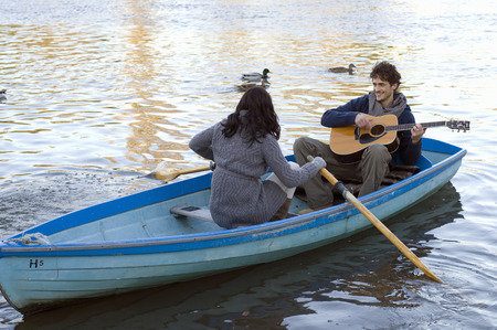 Man playing guitar in row boat LANG_EVOIMAGES