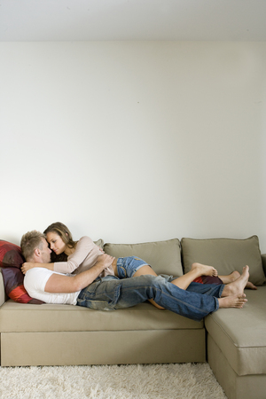 provocative couple: Young couple lying on sofa and embracing