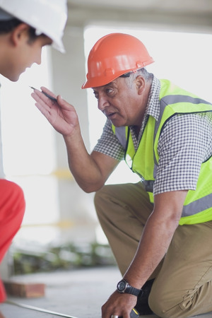Old worker talking to young worker