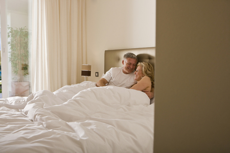 tenderly: Mature couple embracing tenderly in bed