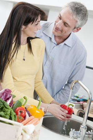 Couple washing fresh vegetables