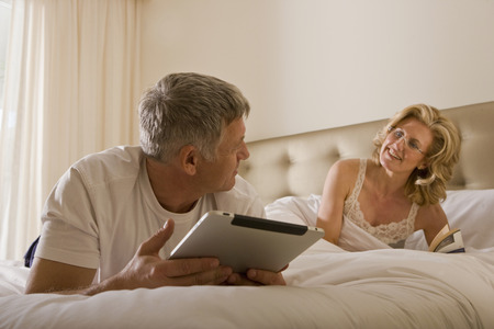 rejoices: Man using tablet computer on bed
