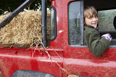 leaning on the truck: Young boy smiling in the back of 4x4
