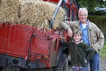 leaning on the truck: Grandfather and Grandson by 4x4 on farm