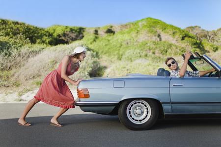 Woman pushing car as boyfriend steers