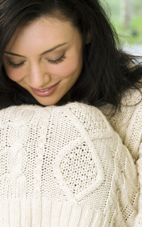 timidity: Woman pulling sweater over her knees