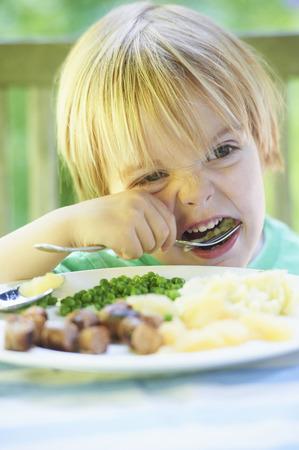 aggressively: Boy eating vegetables at dinner