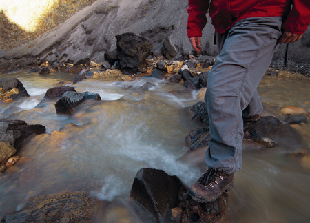 remoteness: Hiker crossing rocky river