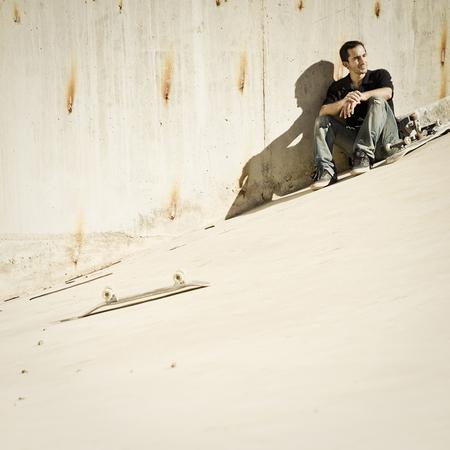 accomplishes: Skateboarder sitting on concrete slope