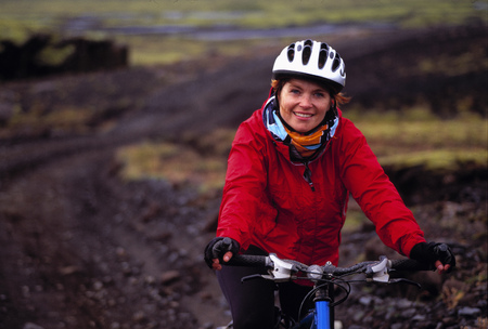 Woman riding mountain bike on dirt road LANG_EVOIMAGES