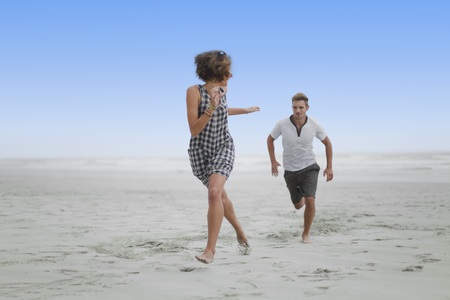 turn away: Couple chasing each other on beach