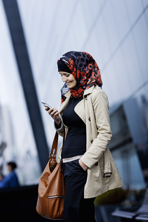 one eyed: Woman in headscarf using cell phone LANG_EVOIMAGES